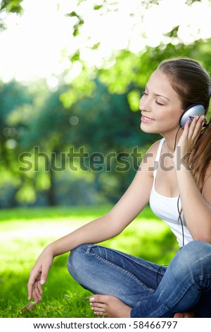 A young girl listens to music with headphones in the park - stock photo