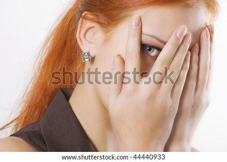 A young girl looking at the camera between her fingers - stock photo