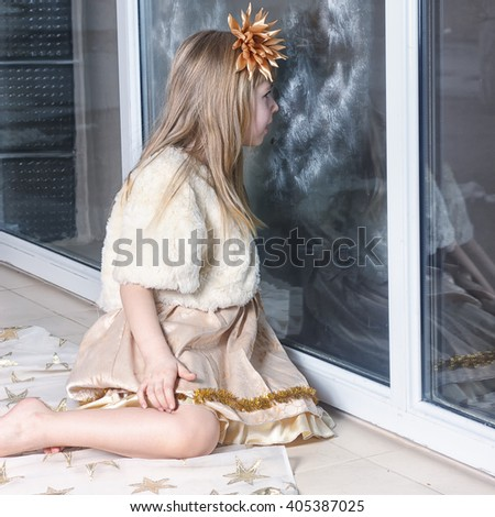 a young girl looking out the window, excited to see snow outside. - stock photo