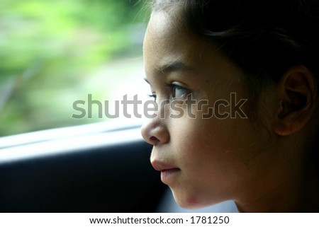 A young girl looking through the window as she travels in a car