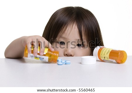 A young girl looks at a pile of pills that was left on a counter. - stock photo