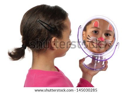 A young girl looks at herself in the mirror after her facial painting. - stock photo