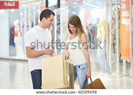 A young girl looks into the shopping bag with men - stock photo