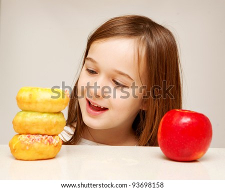 A young girl looks towards unhealthy donuts rather than the healthy apple. - stock photo