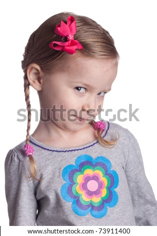 A young girl looks up and to the side at the viewer.  She could be posing a question, thinking or just being cute.