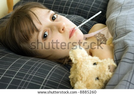 A young girl lying in bed with an illness