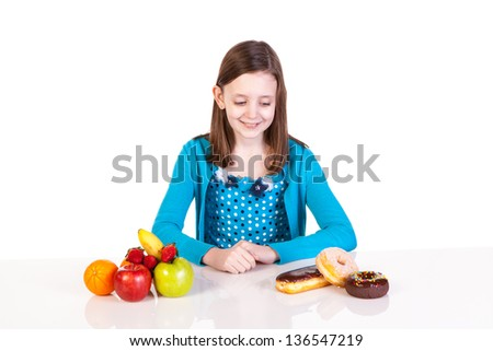 a young girl making a healthy versus junk food decision - stock photo