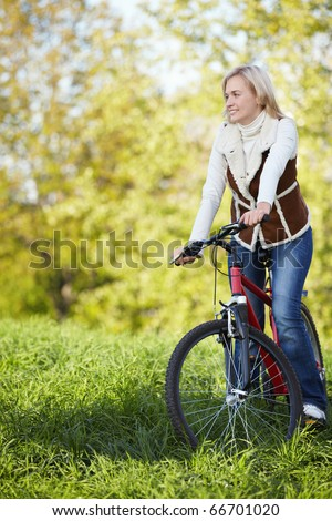 A young girl on a bicycle in the autumn park