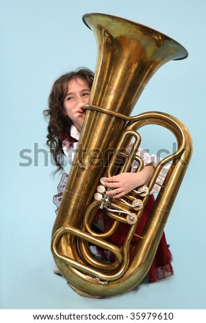 A young girl on her knees trying to play the horn.
