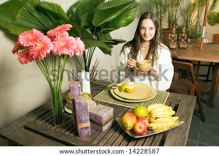 A young girl outside surrounded by plants, fruits, and flowers, holding a cup, smiling for the camera. - horizontally framed - stock photo