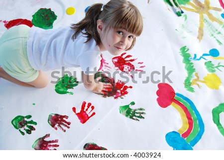 A young girl painting with her hands - stock photo