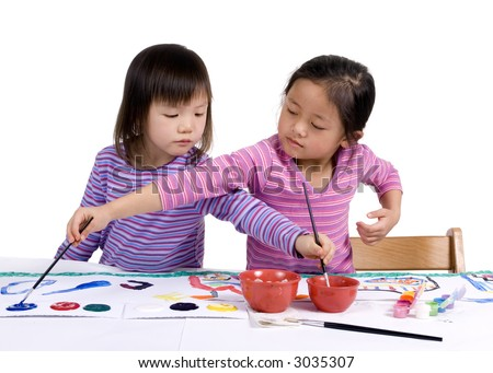 A young girl paints her masterpiece with bright colors. - stock photo