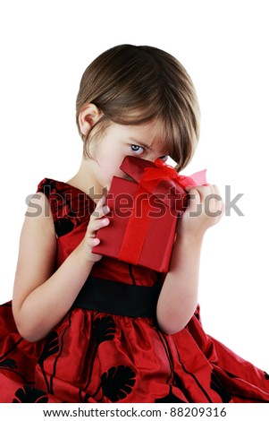 A young girl peeking into a gift she has received isolated against a white background with clipping path included. - stock photo