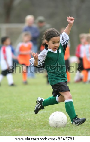 A young girl playing in a soccer league - stock photo