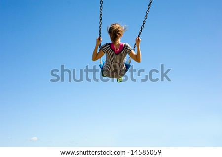 A young girl playing on a swing-set in front of a blue sky.  Girl is swinging very high in swing, with copy space - stock photo