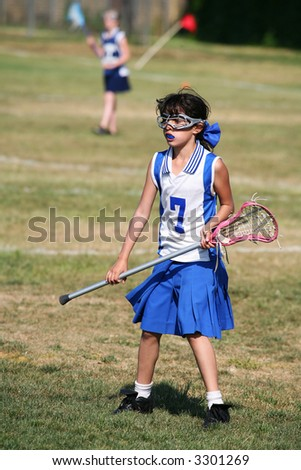 A young girl playing the sport of lacrosse - stock photo