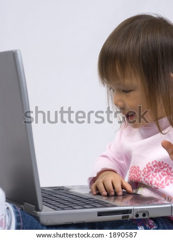 A young girl playing with a laptop computer
