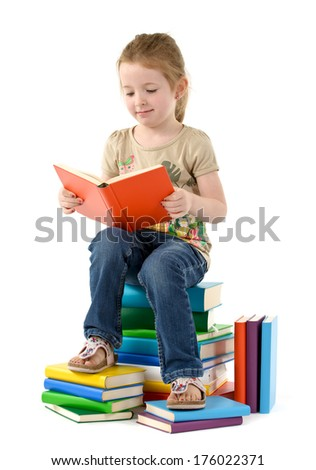 A young girl reading a book while sitting on a stack of books.