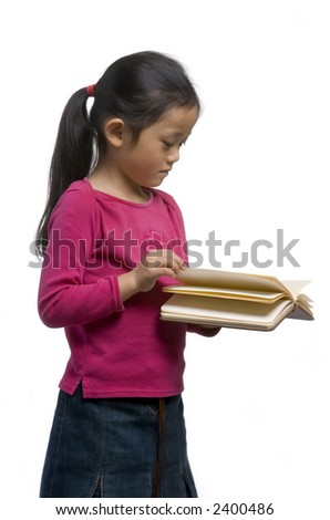A young girl reads a book while standing up - stock photo