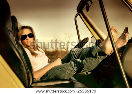 a young girl relaxing in her car - stock photo