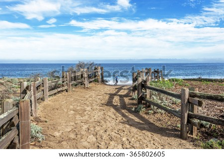 A young girl running along the beach, with aquamarine seas, blue sky & white clouds. In the foreground sand dunes, split rail fence and running trail. Monterey Beach, on the California Central Coast. - stock photo