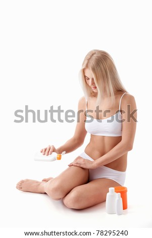 A young girl's body butters cream on a white background - stock photo