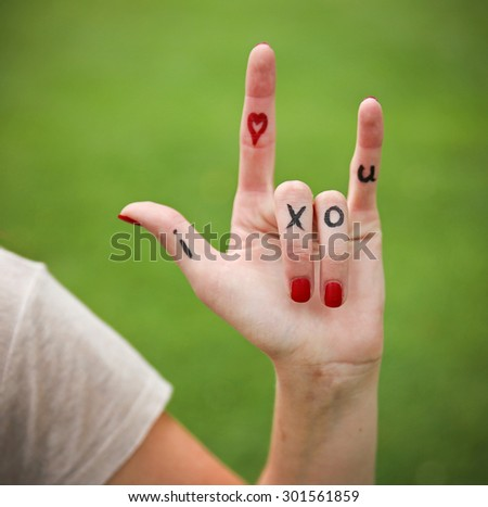 a young girl's hand with lettering i heart x o u written on during summer making the rock on sign - stock photo