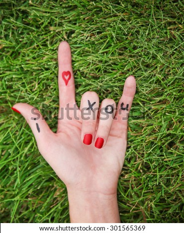 a young girl's hand with lettering i heart x o u written on it in the grass during summer making the rock on sign  - stock photo