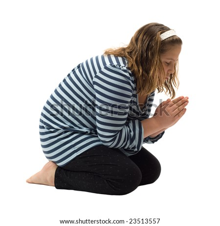 A young girl saying her bedtime prayer, isolated against a white background - stock photo