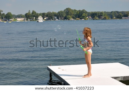 a young girl shows off her bubble making ability at the lake - stock photo