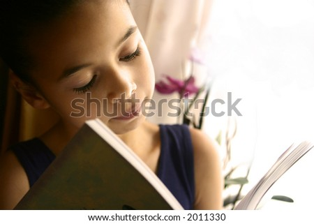 A young girl sitting by the window reading her favourite book, beautifully lit. - stock photo