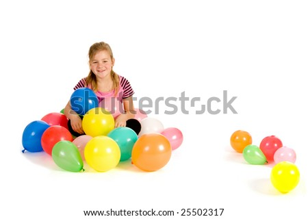 A young girl sitting in balloons on white