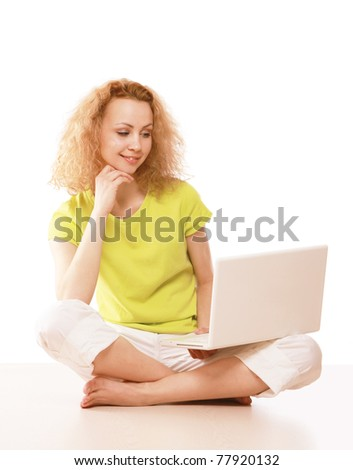 A young girl sitting on the floor with a laptop