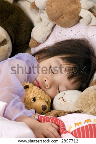 A young girl sleeps with her favorite stuffed animals - stock photo