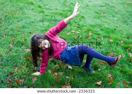 A young girl slips over on very wet grass. - stock photo
