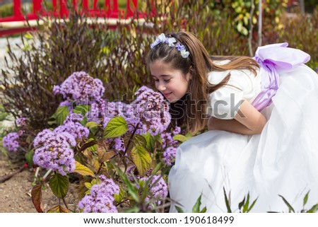 A young girl smelling flowers and celebrating her First Holy Communion - stock photo