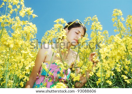 A young girl smelling the flowers of spring - stock photo