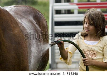 A young girl sprays her horse with refreshing cool water after a ride. - stock photo