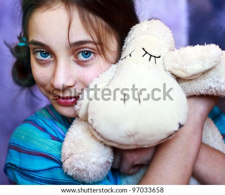 A young girl squeezing hugging her toy lamb - stock photo
