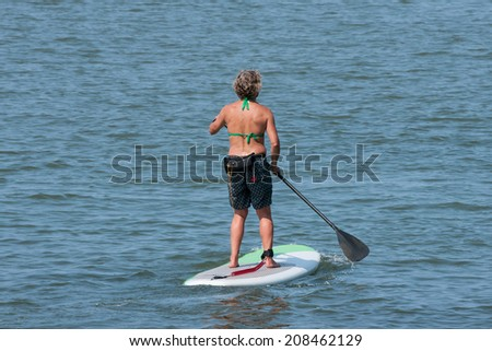A young girl standing on a paddleboard makes her way out into Lake Erie in the harbor at the Port of Cleveland, Ohio