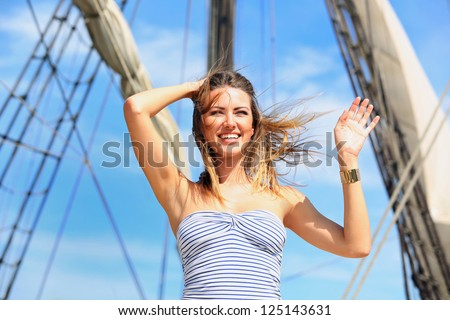 A young girl standing on the pier and affably waving