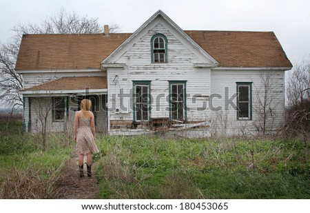 A young girl standing outside an abandoned house
