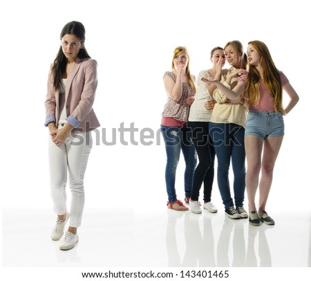 A young girl stands alone on the left edge of the screen, her four girlfriends are in the background and gossip about them. - stock photo