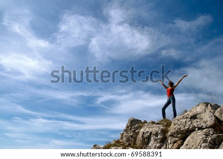 A young girl stands on the edge of a cliff with a beautiful sky with clouds