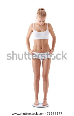 A young girl stands on the scales isolated - stock photo