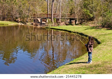 A young girl stands on the shoreline of a lake and fishes alone - stock photo