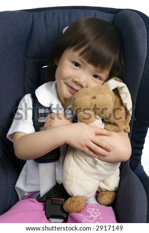 A young girl strapped into a car seat hold her bunny to keep it safe.