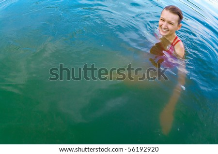 a young girl swimming in the river on a sunny day
