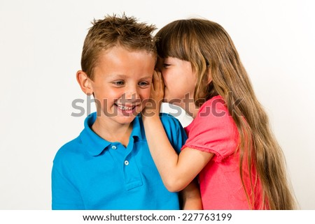 A young girl telling a secret to a young boy. Isolated on white background. - stock photo