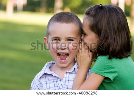 A young girl telling her brother a secret - whispering it to him.